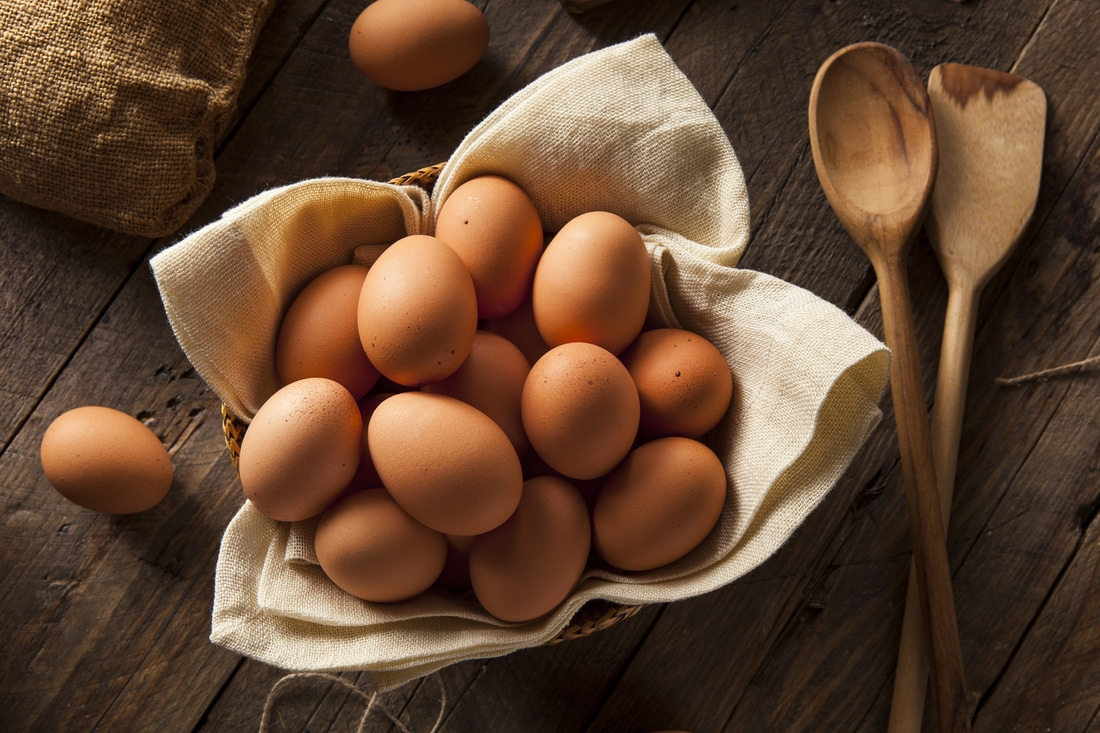 Brown eggs in a basket on a wood background
